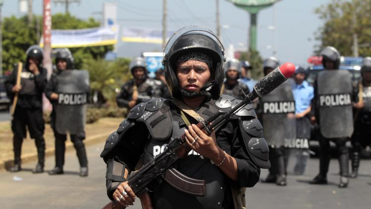 A riot policewoman stands with her weapon on a street during an International Women's Day march in Managua