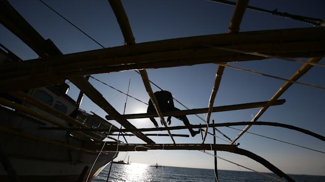 In this May 6, 2013 photo, a Filipino fisherman straps bamboo poles as a fishing boat undergoes maintenance in the coastal town of Masinloc, Zambales province, northwestern Philippines.  Since China took control of the Scarborough Shoal last year, which Beijing calls Huangyan Island, Filipino fishermen say Chinese maritime surveillance ships have shooed them from the disputed waters in the South China Sea and roped off the entrance to the vast lagoon that had been their fishing paradise for decades, forcing many of them to sell, abandon or have their idle boats repaired. Now, they say, they can't even count on the Chinese to give them shelter there from a potentially deadly storm. (AP Photo/Aaron Favila)