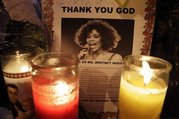 Candles burn at a memorial at a memorial to Whitney Houston outside New Hope Baptist Church in Newark, N.J., early Saturday, Feb. 18, 2012. Whitney Houston's funeral will take place later Saturday at the church where she sang in the choir as a girl. (AP Photo/Mel Evans)