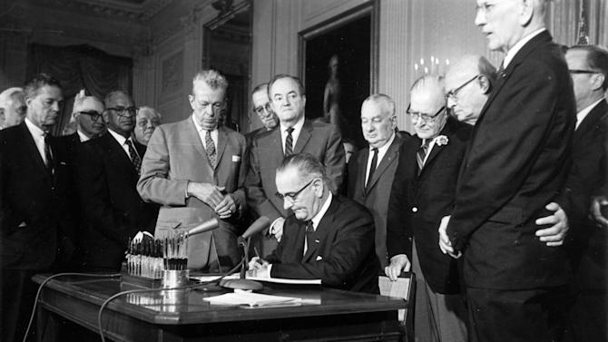 FILE - This July 2, 1964 file photo shows President Lyndon Baines Johnson signing the civil rights bill, in the East Room of the White House in Washington. With Washington mired in congressional gridlock, it's become trendy in the nation's capital to long for the days when LBJ could cajole or strong-arm lawmakers on both sides of the aisle into backing his legislative priorities. Implicit in those bouts of nostalgia is a sentiment that frustrates President Barack Obama and his advisers: the notion that the current commander-in-chief could break Washington's logjam if only he emulated Johnson's hands-on approach to dealing with Capitol Hill. Standing from left, are: Sen. Everett Dirksen, R-Ill; Rep. Clarence Brown, R-Ohio; Sen. Hubert Humphrey, D-Minn; Rep. Charles Halleck, R-Ind; Rep. William McCullough, R-Ohio; and Rep. Emanuel Celler, D-NY. (AP Photo, File)