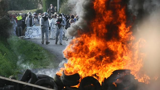 Protesters stand by a burning barricade near Lieusant, Normandy, Wednesday, Nov. 23, 2011. Police have used tear gas on hundreds of nuclear protesters trying to head off the departure of a train carrying recycled uranium to Germany. Some 300 protesters clashed with police  in fields in the village of Lieusaint, outside Valognes, site of the rail depot from where the train loaded with the uranium treated by Areva was expected to depart.(AP Photo/David Vincent)