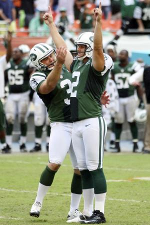 New York Jets punter Robert Malone (3) congratulates kicker Nick Folk (2) after Folk made a field goal during overtime of an NFL football game against the Miami Dolphins, Sunday, Sept. 23, 2012, in Miami. The Jets won 23-20. (AP Photo/Wilfredo Lee)