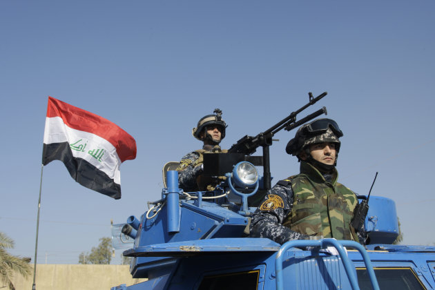 FILE - In this Nov. 22, 2011 file photo, the Iraqi flag waves while federal police parade in Baghdad. A report by the U.S. Special Inspector General for Iraq Reconstruction, to be released Monday, July 30, 2012, found that the American Embassy in Baghdad never got a written commitment for Iraq to participate in what initially was envisioned as a five-year, multibillion-dollar effort to train security forces after the U.S. military left last December. (AP Photo/Khalid Mohammed, File)