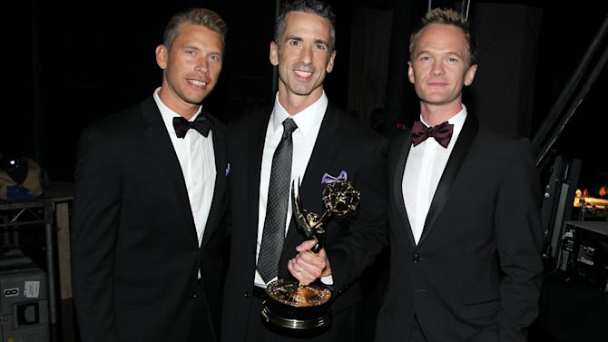 Terry Miller, Dan Savage and Neil Patrick Harris, from left to right, are seen backstage with the Governors Award at the 2012 Creative Arts Emmys at the Nokia Theatre on Saturday, Sept. 15, 2012, in Los Angeles. (Photo by Matt Sayles/Invision/AP)