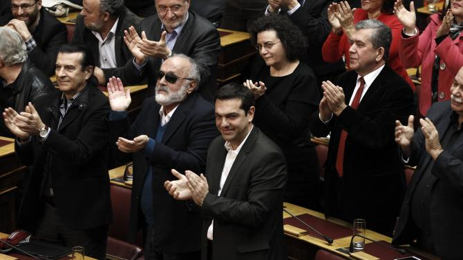 Tsipras, opposition leader and head of radical leftist Syriza party, and his party's lawmakers applaud after the last round of a presidential vote in Athens