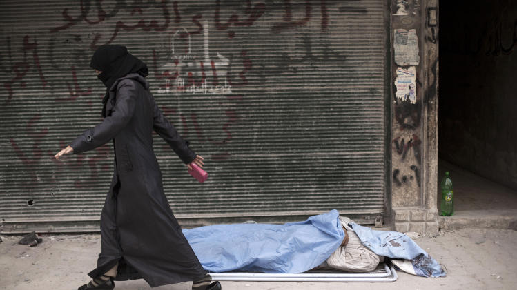 In this Wednesday, Oct. 10, 2012 photo, a Syrian woman walks past a body in front of Dar El Shifa Hospital, Aleppo, Syria. (AP Photo/ Manu Brabo)
