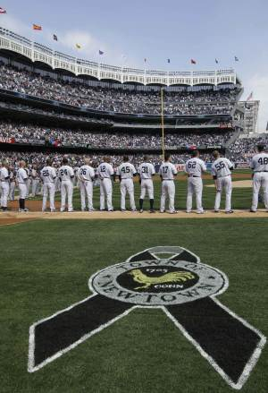 A logo dedicated to the town of Newtown,  Connecticut, is painted on the grass as players line up during an honor guard and tribute to the Newtown school shooting victims at an Opening Day baseball game at Yankee Stadium in New York, Monday, April 1, 2013.  (AP Photo/Kathy Willens)