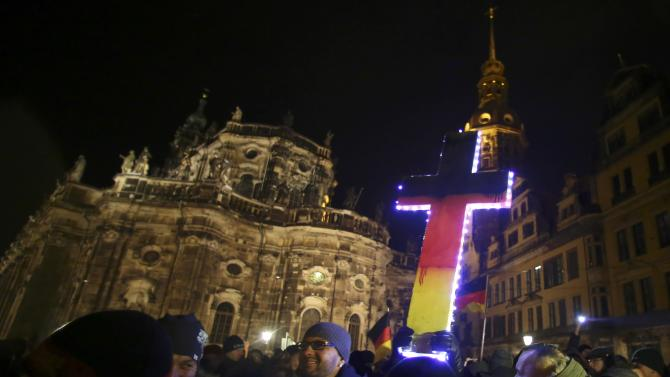 "Participants hold a cross painted in the colours of German national flag during a demonstration called by anti-immigration group PEGIDA, a German abbreviation for ""Patriotic Europeans against the Islamization of the West"", in Dresden"