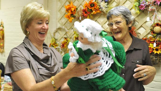 In this Tuesday, Sept. 18, 2012 photo, Republican candidate for U.S. Senate Linda McMahon, left, looks at a doll made by Bernice Niro during a visit to the Naugatuck Senior Center in Naugatuck, Conn. Wealthy former pro wrestling executive McMahon is shifting her image from groin-kicking CEO to grandmother in her second bid for a Senate seat from Connecticut. Polls show the strategy seems to be working against three-term Democratic congressman Chris Murphy.(AP Photo/Jessica Hill)