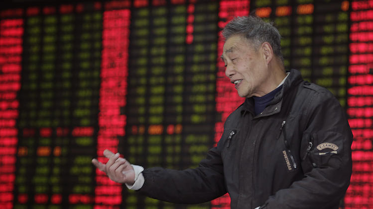 An investor gestures at a private securities company on Monday March 4, 2013 in Shanghai, China. Uncertainty about the outcome of a budget battle in Washington pushed Asian stock markets lower on Monday. (AP Photo/Eugene Hoshiko)