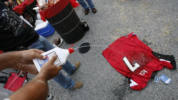 """Atlanta Falcons fan Mike Laymon, Douglasville, GA., squirts lighter fluid on a Michael Vick jersey as he prepare to set it on fire in the """"Gulch,"""" a fan parking lot outside the Georgia Dome, before the Falcons play the Eagles on Sunday, Sept. 18, 2011. He started his last game in the Georgia Dome for the Falcons in 2006, a loss in which he played badly, but Michael Vick still has a powerful hold on some Falcons fans both pro and con.   (AP Photo/Atlanta Journal-Constitution, Curtis Compton)"""