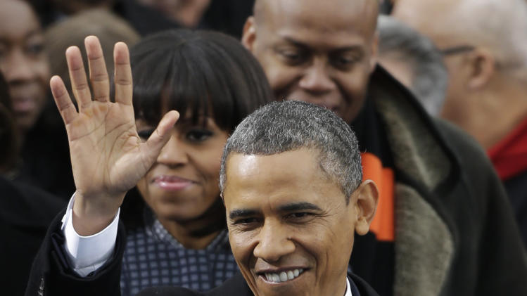 With his wife Michelle at his shoulder, President Barack Obama waves to crowds gather for his ceremonial swearing-in at the U.S. Capitol during the 57th Presidential Inauguration in Washington, Monday, Jan. 21, 2013. (AP Photo/Pablo Martinez Monsivais)