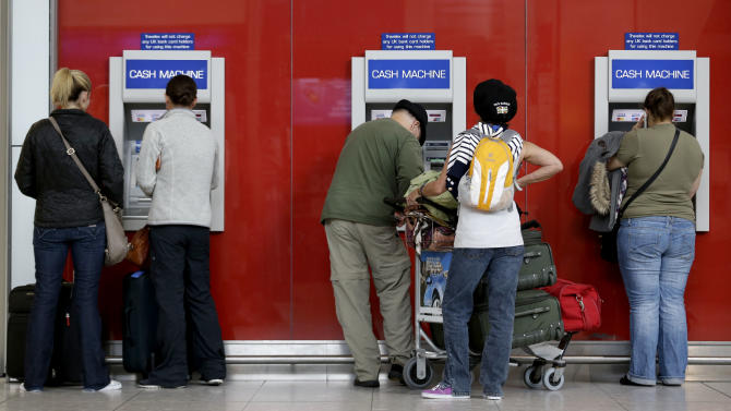 Travelers withdraw cash from ATM machines at Heathrow Airport Wednesday, July 18, 2012 as London prepares for the 2012 Summer Olympics.  Tourists be warned: The Olympics crush has begun in London _ and so has the scramble for cold, hard cash in the pricey British capital. Lines are getting longer at ATMs, visitors are in sticker shock over British prices and some befuddled tourists are wondering what currency to use. Stores in the Olympic Park only accept certain credit cards and a British financial authority is even recommending that tourists make sure to bring British pounds with them. (AP Photo/Charlie Riedel)