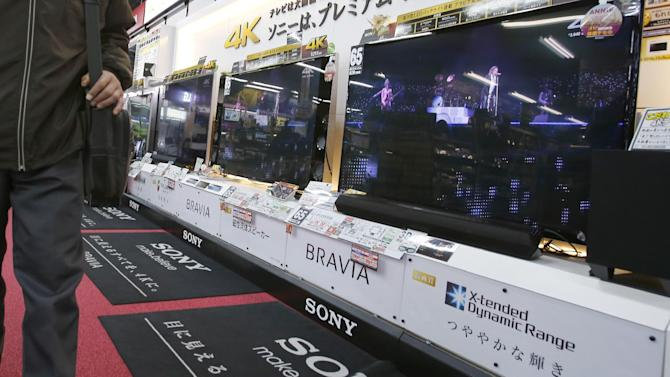 """In this Thursday, Dec. 25, 2014 photo, a shopper walks by Sony's Bravia flat panel TV sets on display at a Tokyo electronics store in Tokyo. Sony's iconic gadgetry and the star appeal of Hollywood may have appeared to be a perfect match when the electronics giant bought Columbia Pictures in 1989. A quarter century later, it's apparent that Sony Corp. has not attained the magic synergy it was hoping for. The stolid silence of Sony's Tokyo headquarters over the hoopla surrounding """"The Interview"""" underscores the longstanding divide between the Japanese parent company and its U.S.-led and -run motion pictures subsidiary, successor to Columbia Pictures. (AP Photo/Shizuo Kambayashi)"""