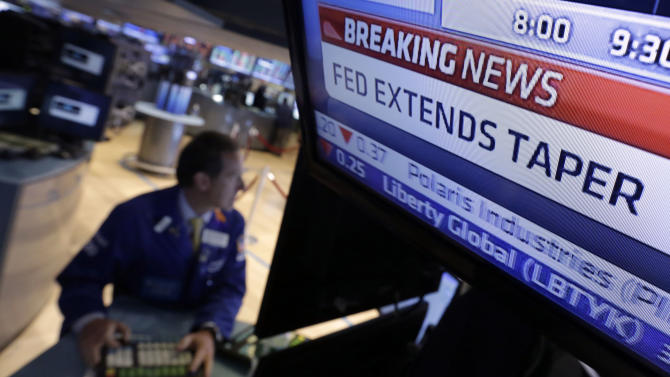 FILE - In this June 18, 2014 file photo, a television monitor at a trading post on the floor of the New York Stock Exchange shows the decision of the Federal Reserve. Like with other higher-risk investments, investors have pulled back from junk, or high yield, bonds because they worry about the end of the Federal Reserve's policy near-zero interest rates. Investors expect the central bank to raise rates sometime next year, and that means the value of bonds currently held in portfolios will fall. (AP Photo/Richard Drew, File)