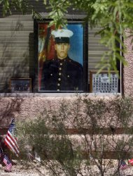 In this photo taken June 9, 2011, a portrait of Marine Jose Guerena Ortiz sits on display in the window of his home in Tucson, Ariz. Guerena was shot and killed on May 5, 2011, by the Pima County Sheriff's Department. The Sheriff's Department said its SWAT team was at the home because they suspected Guerena of being involved in a drug-trafficking organization that specialized in ripping off smugglers. The SWAT team fired 71 times, riddling Guerena 22 times, while his wife and child cowered in a closet. (AP Photo/Matt York)