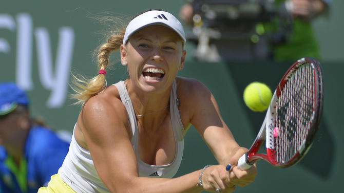Caroline Wozniacki, of Denmark, makes a return against Maria Sharapova, of Russia, during their match at the BNP Paribas Open tennis tournament, Sunday, March 17, 2013, in Indian Wells, Calif. (AP Photo/Mark J. Terrill)