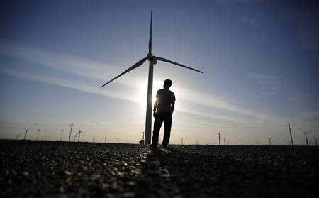 A worker stands as he looks at a wind turbine used to generate electricity, at a wind farm in Guazhou, 950km northwest of Lanzhou, Gansu Province