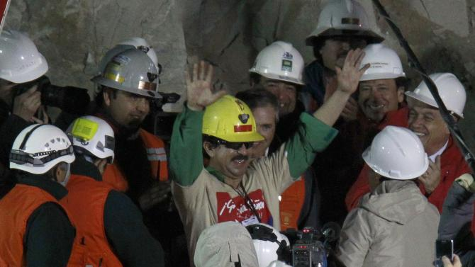 ** ADVANCE FOR USE THURSDAY, DEC. 23, 2010 AND THEREAFTER ** FILE - In this Wednesday Oct. 13, 2010 file picture, rescued miner Juan Andres Illanes Palma, third miner to be rescued, reacts upon his arrival to the surface from the collapsed San Jose gold and copper mine where he was trapped with 32 other miners for over two months near Copiapo, Chile at the San Jose Mine near Copiapo, Chile. (AP Photo/Roberto Candia)