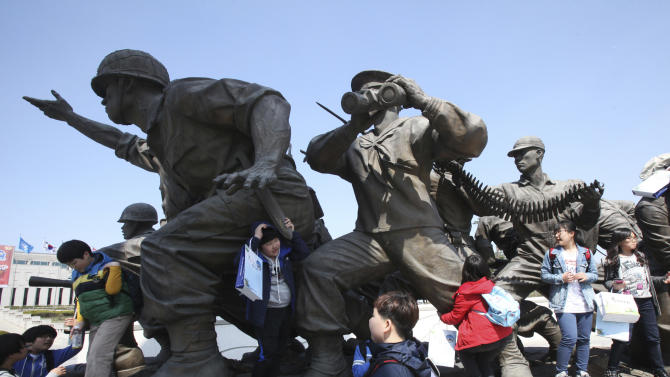 South Korean elementary school students play around the statues of soldiers at a monument in remembrance of the Korean War at the Korea War Memorial Museum, in Seoul, South Korea, Thursday, April 18, 2103. North Korea on Thursday demanded the withdrawal of U.N. sanctions and the end of U.S.-South Korea military drills as preconditions for the resumption of talks meant to defuse tension on the Korean Peninsula. (AP Photo/Ahn Young-joon).