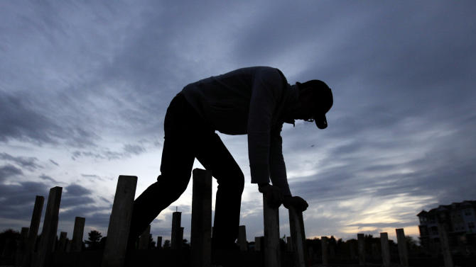 In this Thursday, Oct. 11, 2012, photo, Ford Smith works on a new home under construction in Chicago. U.S. builders increased their spending on construction projects in October by the largest amount in five months, led by a surge in housing.  (AP Photo/Nam Y. Huh)
