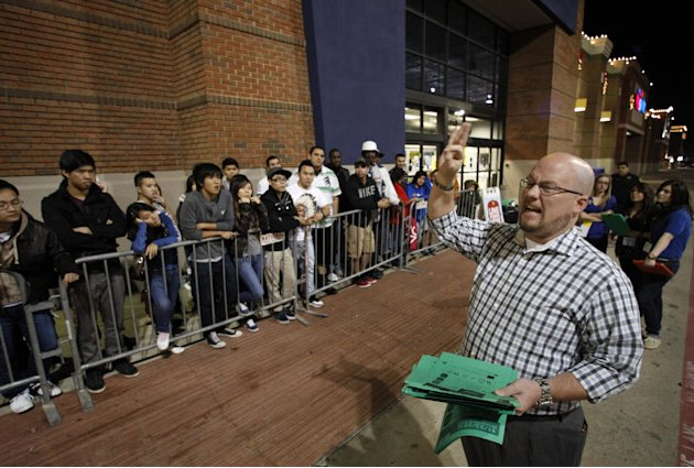 Best Buy general manager Shaun Ogdie, right,  gives instructions to shoppers before handing out  sale vouchers on popular eletronics items before the store opened at midnight Thursday Nov. 22, 2012, i
