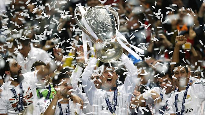 Real's Cristiano Ronaldo, centre, lifts the Champion League trophy, at the end of the Champions League final soccer match between Atletico Madrid and Real Madrid, at the Luz stadium, in Lisbon, Portugal, Saturday, May 24, 2014
