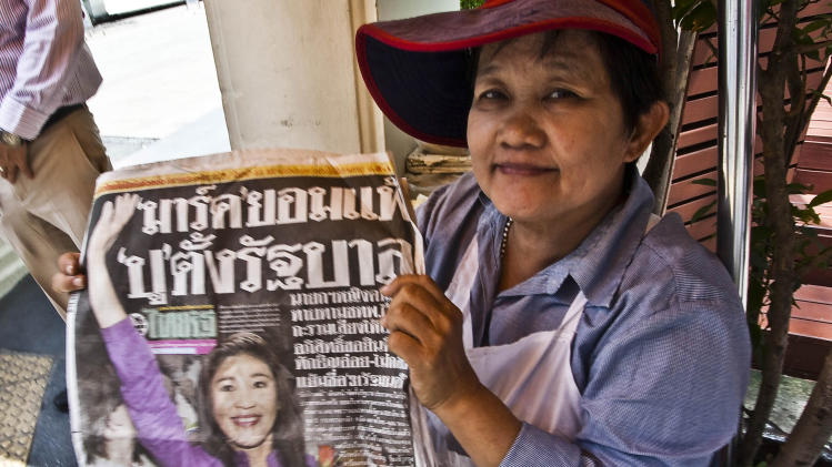 A Thai woman holds a newspaper Monday, July 4, 2011, with news of the Pheu Thai party's landslide victory over Prime Minister Abhisit Vejjajiva's Democrat Party in yesterday's general election. With the victory Yingluck Shinawatra, leader of the Pheu Thai party, is tapped to become the next prime minister of Thailand. (AP Photo/David Longstreath)