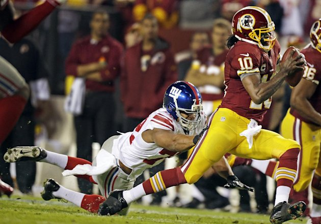 New York Giants defensive end Osi Umenyiora (72) reaches for Washington Redskins quarterback Robert Griffin III (10) during the first half of an NFL football game in Landover, Md., Monday, Dec. 3, 201