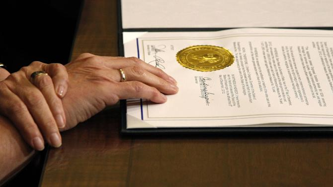 Gov. Chris Gregoire rests her hands on the document after signing into law Referendum 74, a citizen-passed measure that legalizes same-sex marriage in the state, Wednesday, Dec. 5, 2012, in Olympia, Wash. Gregoire and Secretary of State Sam Reed both signed the document, which allows gay couples to marry beginning Dec. 9. (AP Photo/Elaine Thompson)