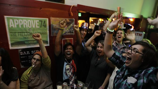 Supporters of President Barack Obama, react to news reports of his projected re-election, Tuesday, Nov. 6, 2012, at a bar in Seattle's Capitol Hill neighborhood. (AP Photo/Ted S. Warren)