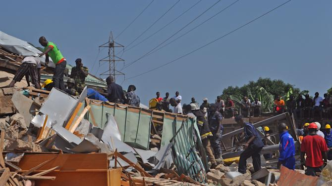 Rescue workers among the remainder of a collapsed building in Accra, Ghana, Wednesday, Nov. 7, 2012.  A five-story shopping center built earlier this year in a bustling suburb of Ghana's capital collapsed Wednesday, killing at least one person and leaving several dozen people trapped in the rubble, authorities and eyewitnesses said. (AP Photo/ Laura Burke)