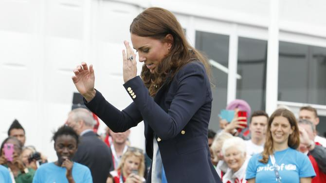 Britain's Catherine, Duchess of Cambridge plays South African games 'Three Tins' during a visit to the Commonwealth Games Village at the 2014 Commonwealth Games in Glasgow