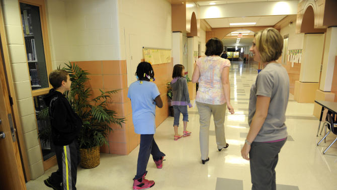 Third grade students walk out of their classroom after taking the ISTEP test at Emmons Elementary School in Mishawaka, Ind. Wednesday May 1, 2013. Issues with the computer based testing program have caused some problems with the ISTEP test. The Indiana Department of Education said in a statement that administration of the ISTEP+ exams' online portion resumed Wednesday morning, but that schools are being asked to decrease their daily test load to 50 percent of normal levels until further notice.  (AP Photo/Joe Raymond)