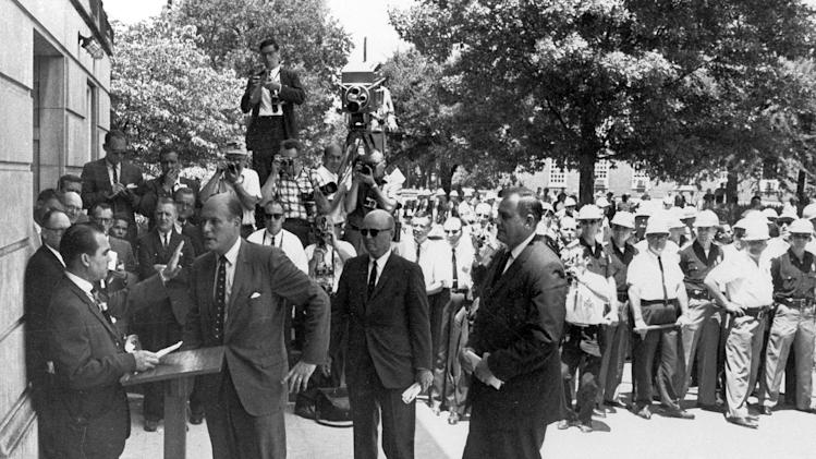 FILE - In this June 11, 1963 file photo, Alabama Gov. George C. Wallace, left, raises his hand to stop U.S. Deputy Attorney General Nicholas Katzenbach as Wallace stands in front of a door to keep blacks from enrolling at the University of Alabama in Tuscaloosa, Ala. Katzenbach, who held influential posts in the Kennedy and Johnson administrations and played a prominent, televised role in federal desegregation efforts in the South, died Tuesday, May 8, 2012. He was 90. (AP Photo/Tuscaloosa News, Calvin Hannah)