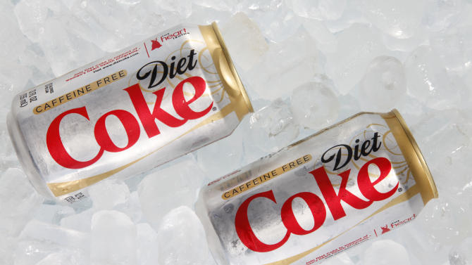 This Monday, Oct. 15, 2012 photo shows two cans of Caffeine Free Diet Coke on ice in Surfside, Fla. Coca-Cola is expected to report earnings, Tuesday, Feb. 12, 2013. (AP Photo/Wilfredo Lee)