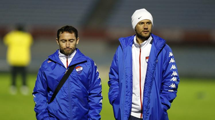 Lusardi and Bareiro of Paraguay's Nacional walk in the Centenario stadium in Montevideo