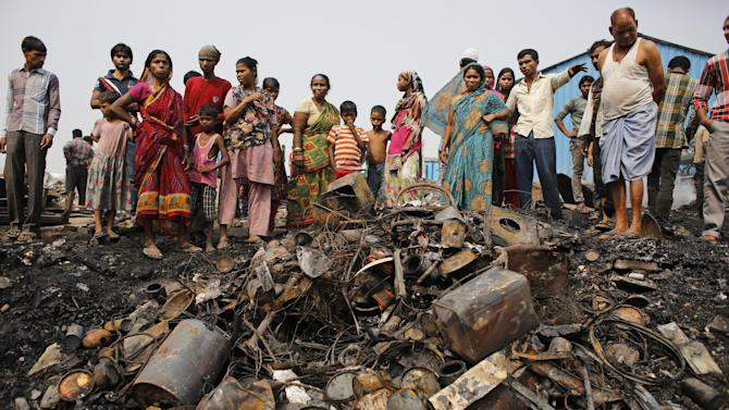 Indians stand near a pile of utensils that lay covered in ash after a fire at a slum area in New Delhi, India, Friday, Oct. 24, 2014. The cause of the fire is unknown. No casualties have been reported so far. (AP Photo/Altaf Qadri)