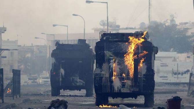 Riot police armoured personnel carrier is seen on fire from a molotov thrown by protesters during clashes in the village of Bilad Al Qadeem south of Manama