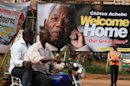Men ride a motor cycle taxi past a poster of late author Chinua Achebe, in Awka, Nigeria, Wednesday, May 22, 2013. People gathered Wednesday to celebrate the life of author Chinua Achebe, who died in March at the age of 82. His family plans to bury the literary icon Thursday in his home village of Ogidi. (AP Photo/Sunday Alamba)