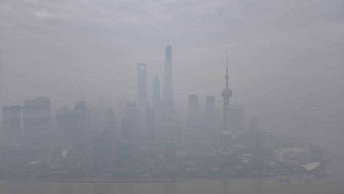 Boats pass along the Huangpu River next to the financial area of the Pudong New District amid heavy smog in Shanghai