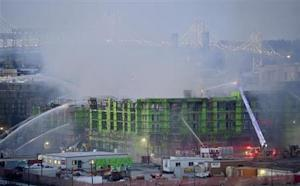 Firefighters spray water on a partially completed apartment building after fire burned through the construction site in San Francisco