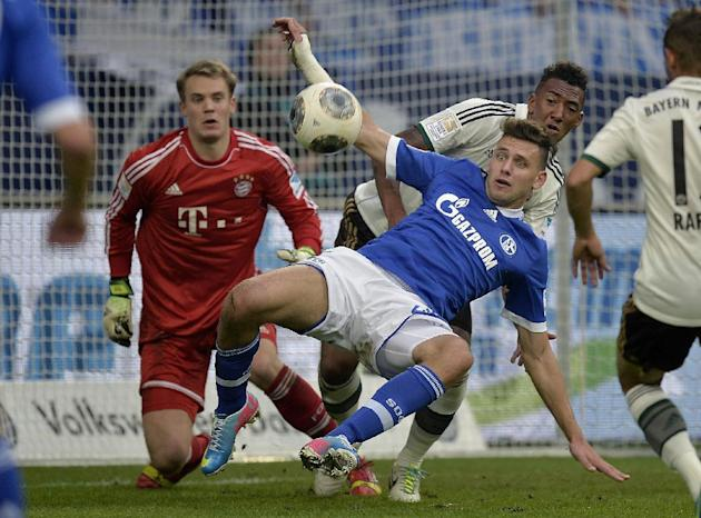Schalke's Adam Szalai of Hungary, center, Bayern goalkeeper Manuel Neuer, left, and Bayern's David Alaba of Austria challenge for the ball during the German soccer Bundesliga match between FC Schalke
