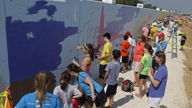 In a June 4, 2011 photo, community members take part in the Make Your Mark mural project, in Chesterfield, Mo.  Over 2000 community members participated in painting the 500 foot mural on the Chesterfield-Monarch Levee flood wall near the Missouri River.  (AP Photo/Tom Gannam)