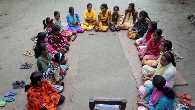 """In this Sept. 30, 2012, photo, a group of Bangladeshi girls, aged between 12 and 17, hold courtyard meeting to learn about menstruation, reproductive health, HIV/AIDS and use of contraceptives at Saghata, a remote impoverished farming village in Gaibandha district, 120 miles (192 kilometers) north of capital Dhaka, Bangladesh. Dozens of """"Info Ladies"""" bike into remote Bangladeshi villages with laptops and Internet connections, helping tens of thousands of people - especially women - get everything from government services to chats with distant loved ones. (AP Photo/A.M. Ahad)"""