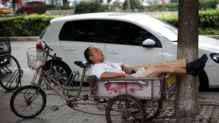 A man takes a nap on a tricycle in Beijing