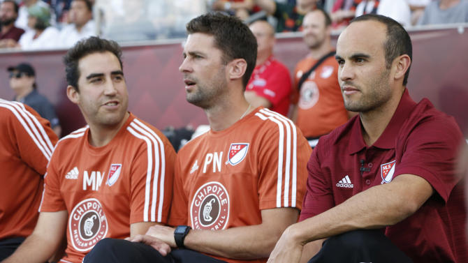 MLS Homegrown Players head coach Landon Donovan, right, takes a seat on the bench with his assistant coaches to watch his team face Club America during the first half of an MLS exhibition soccer game featuring league prospects Tuesday, July 28, 2015, in Commerce City, Colo. The MLS all-star squad will face the Tottenham Hotspur Wednesday night in Dick's Sporting Goods Park in the 20th annual mid-season classic for the league. (AP Photo/David Zalubowski)