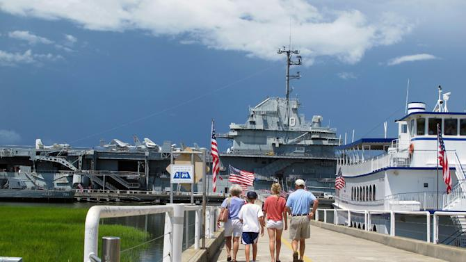 FILE - In this Aug. 7, 2012 file photo, visitors walk toward the USS Yorktown at the Patriots Point Naval and Maritime Museum in Mount Pleasant, S.C. Tourism is an $18 billion industry in South Carolina and a new season is gearing up the week of February 9, 2014 with the Governor's Conference on Tourism and Travel on Hilton Head Island, the Southeastern Wildlife Exposition in Charleston and other events. (AP Photo/Bruce Smith, File)