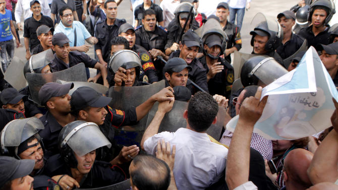 Egyptian anti-riot soldiers scuffle with opposition activists and prevent them from getting close to the Shura Council, the upper house of Parliament, during a protest against the new judicial law in Cairo, Egypt, Saturday, May 25, 2013. (AP Photo/ Amr Nabil)