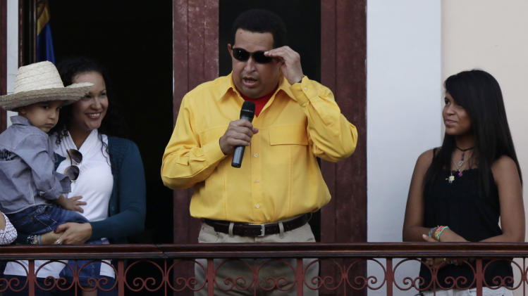 Accompanied by relatives, Venezuela's President Hugo Chavez, center, wears sunglasses as he speaks to supporters from a balcony of Miraflores presidential palace in Caracas, Venezuela, Thursday, July 28, 2011. Chavez sang on a balcony of the presidential palace as he celebrated his 57th birthday before a crowd of supporters, vowing to overcome cancer. (AP Photo/Ariana Cubillos)